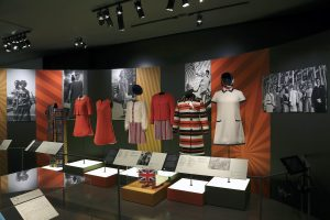 Exhibition display of 1960s short dresses with text panels in front of display