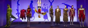 Exhibition display of dressed mannequins in circus outfits, one suspended upside down with shadows in the background