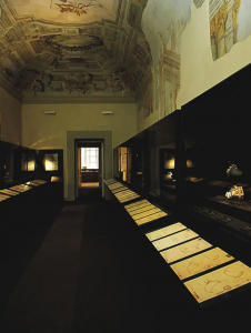 Exhibition display of documents in a cabinet situated in a long room