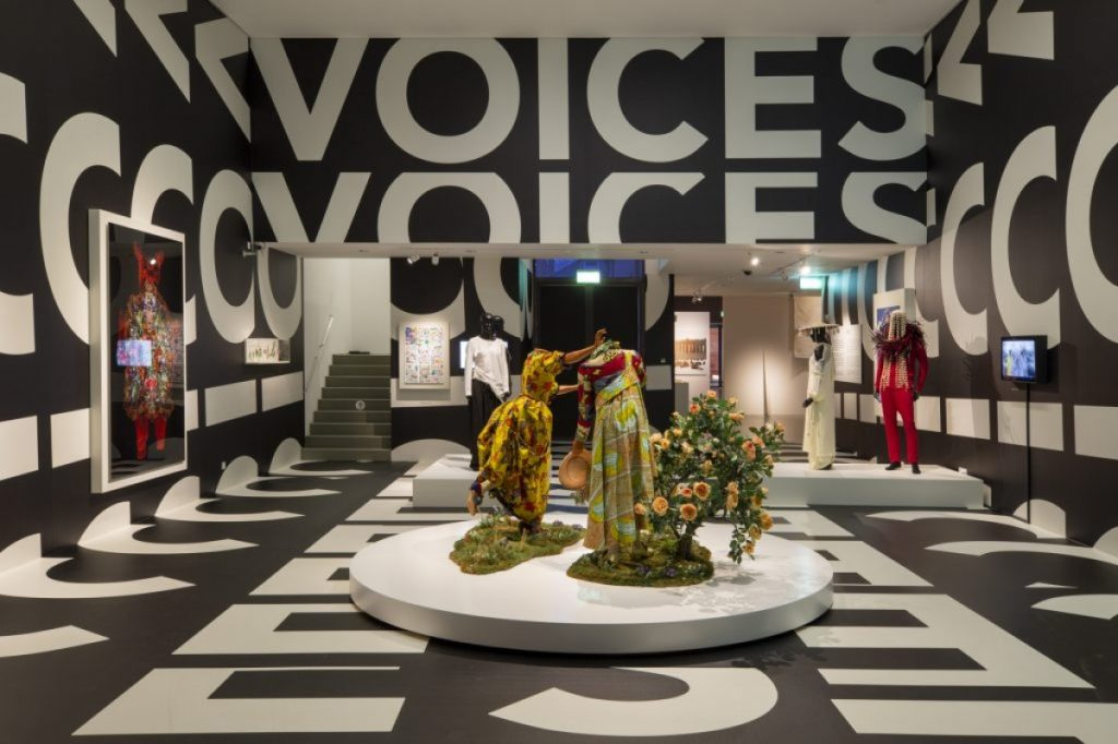 Exhibition display of dressed mannequins in backdrop of black with large white text saying 'voices'