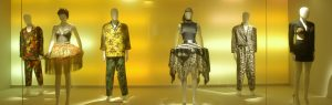 Exhibition display of dressed mannequins with gold backdrop