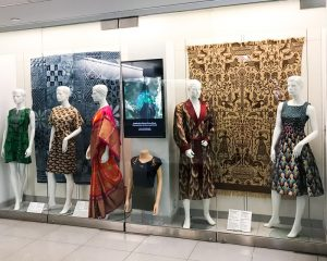 Exhibition display of dressed mannequins in glass case with pattern fabric in background