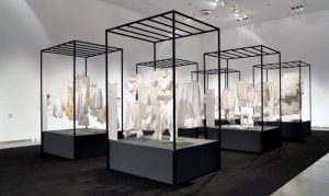 Exhibition display of white garments displayed in metal frames