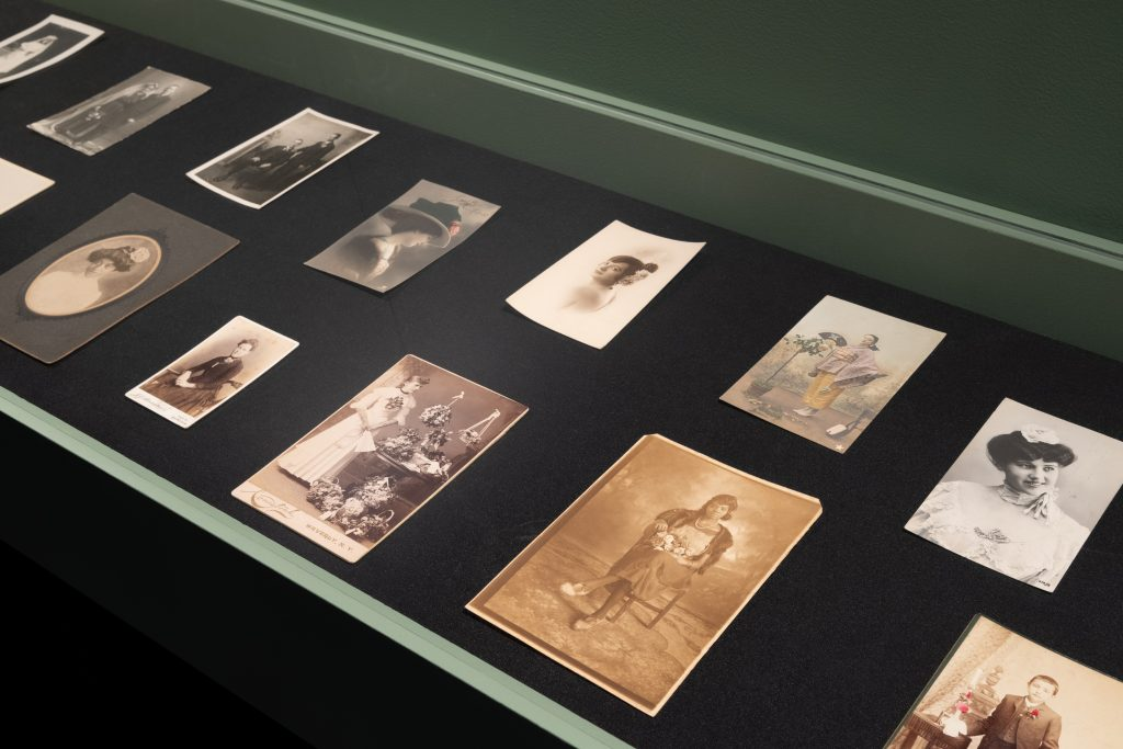 Exhibition display of 19th century looking photographs depicting wearers of roses