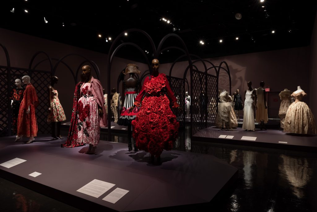 Exhibition display of dressed mannequins in rose decorated dress