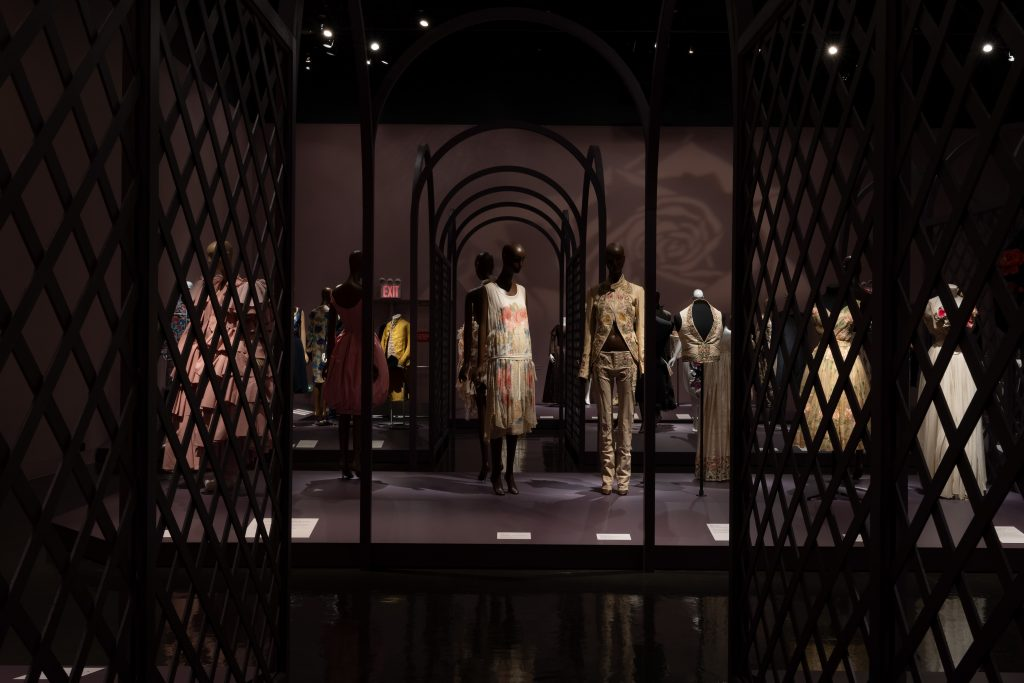 Exhibition display of dressed mannequins behind a trellis