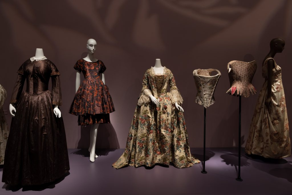 Exhibition display of dressed mannequins in historical rose-patterned garments including corsets