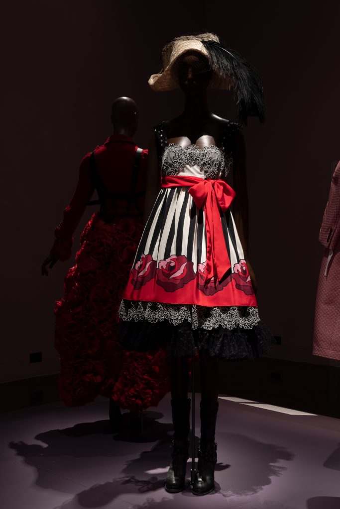 Exhibition display of dressed mannequin in red dress edged with roses