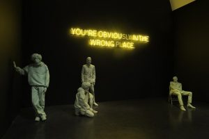 Exhibition display of dressed mannequins with illuminated writing 'you're obviously in the wrong place'