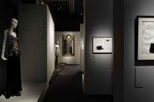 Exhibition display in gallery with mannequin in foreground and background