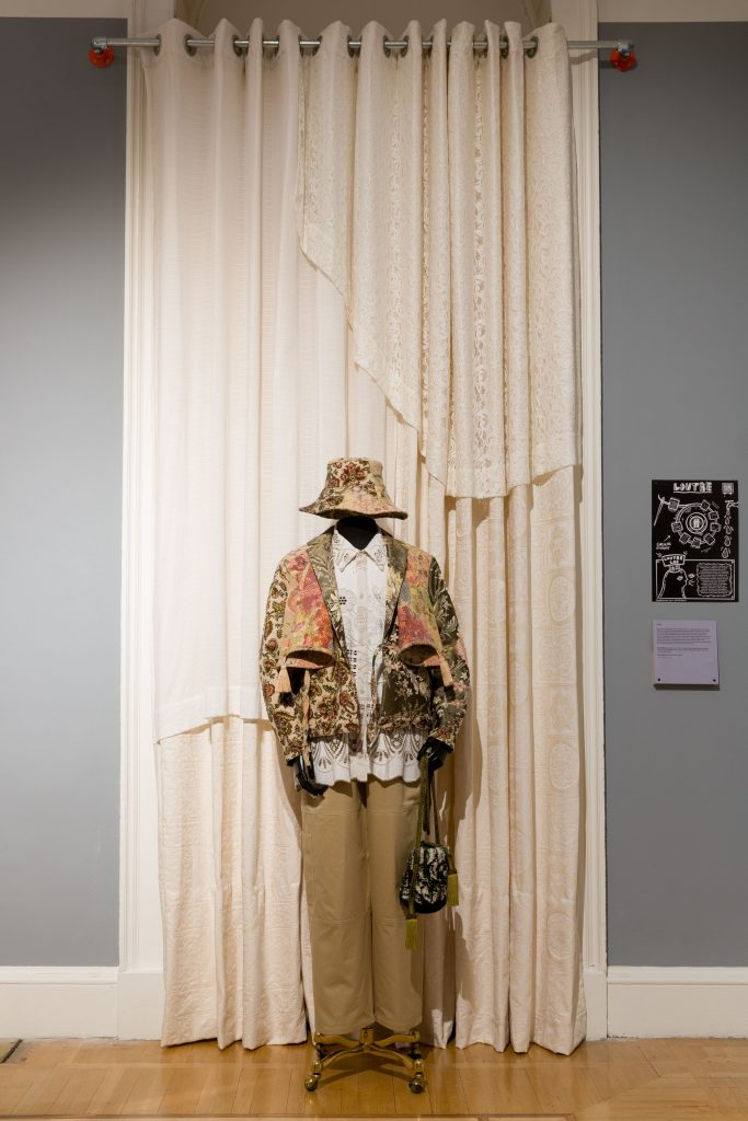 exhibition display mannequin in bucket hat and camel coloured jacket/trousers