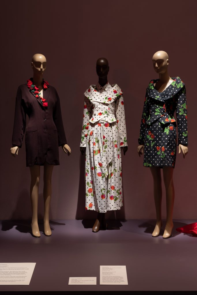 Exhibition display of dressed mannequins with rose-patterned garments